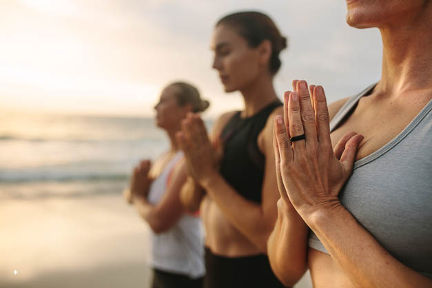 Women practicing yoga on the beach early in the morning. Fitness women standing at the beach meditating with joined palms and closed eyes.